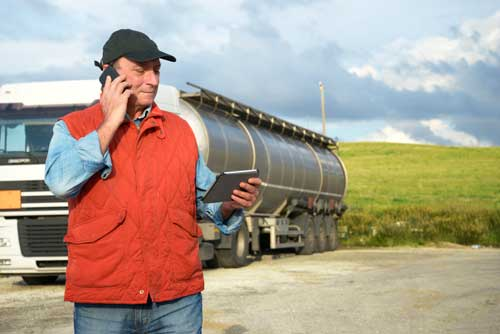 truck driver on phone while reviewing fleet management device
